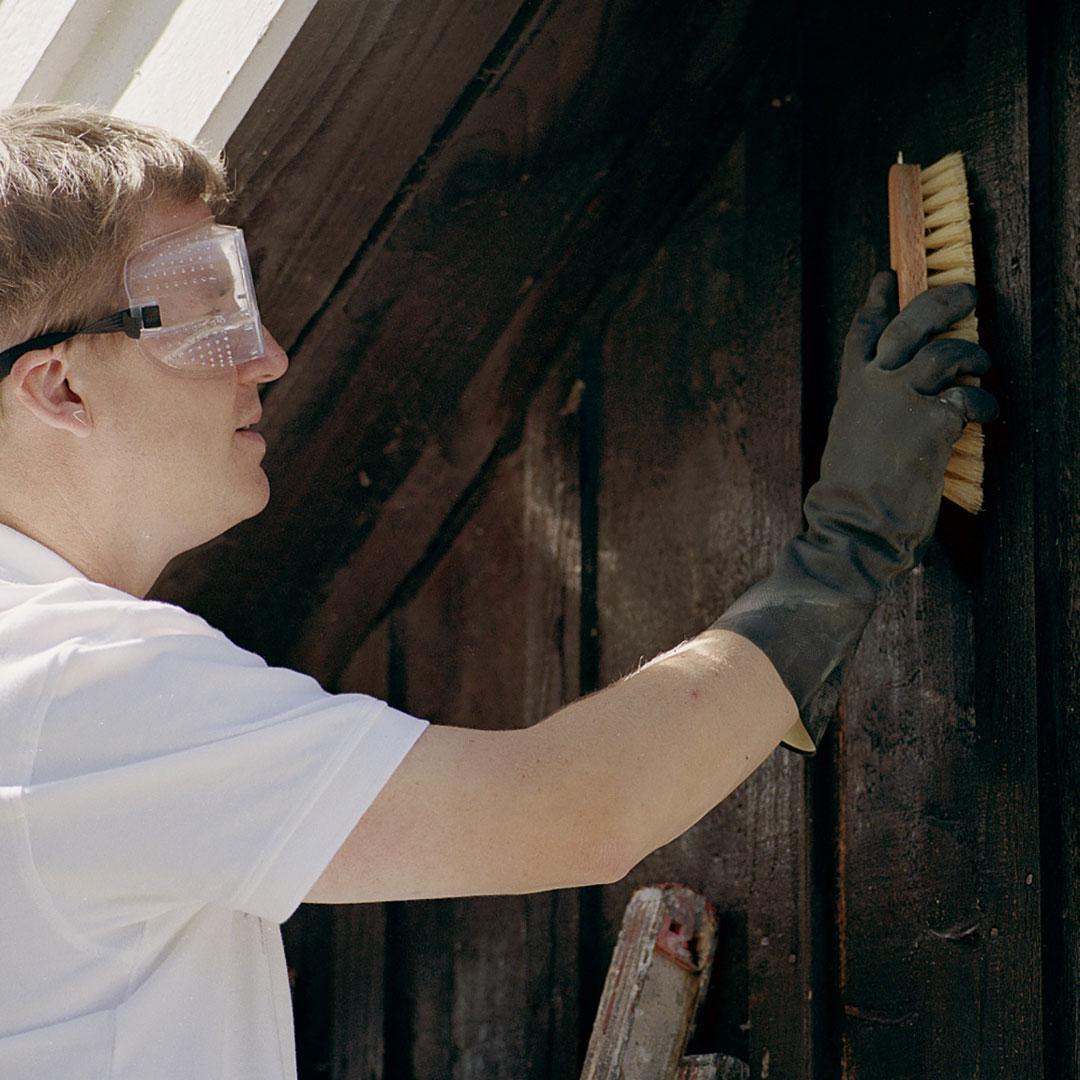 En mann skrubber husveggen
