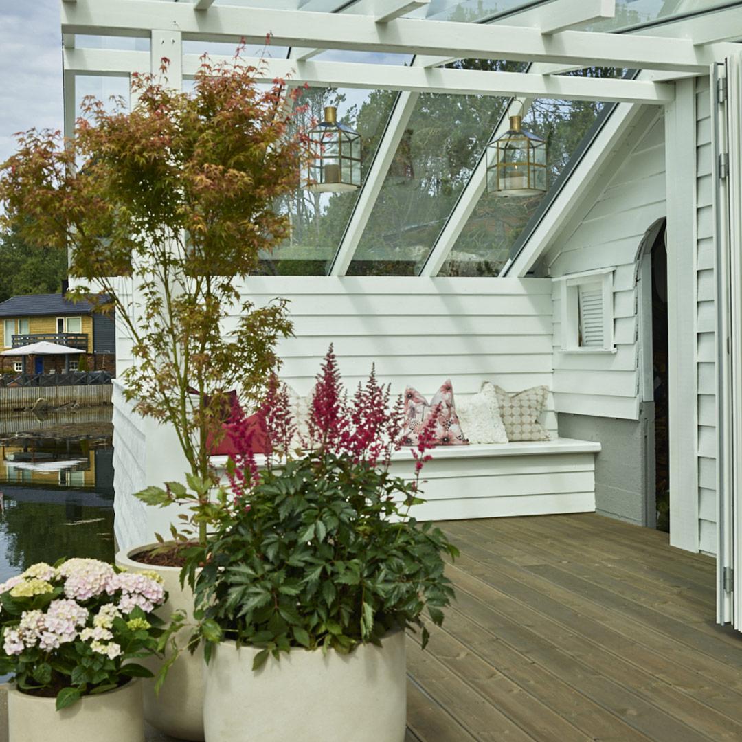 Benk på terrassen med blomster i forgrunnen