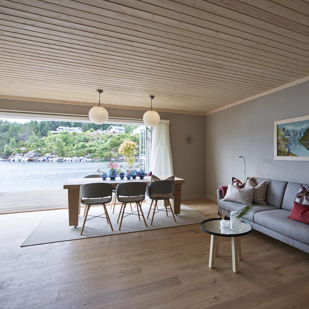 Spiseplassen i stuen med vindu fra gulv til tak bak