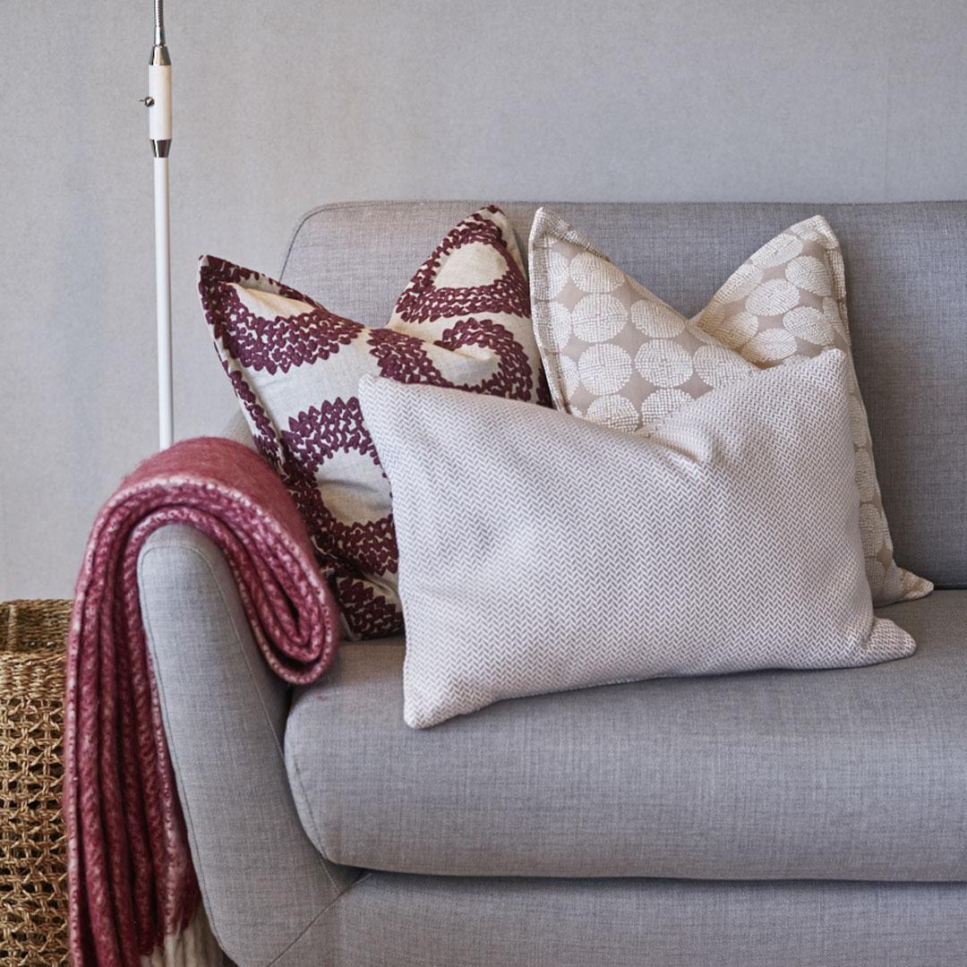 Nærbilde av grå sofa med hvite og rød puter