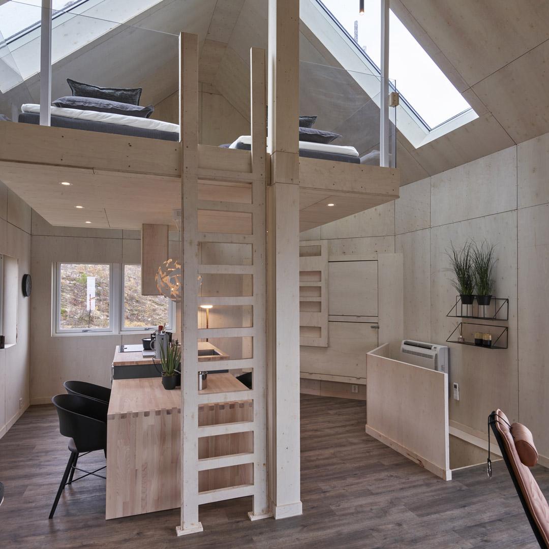 Kjøkken i en hytte med stige til hems i forgrunnen