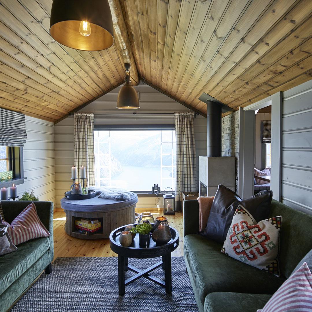 Stue i hytte med sofa og flott utsikt