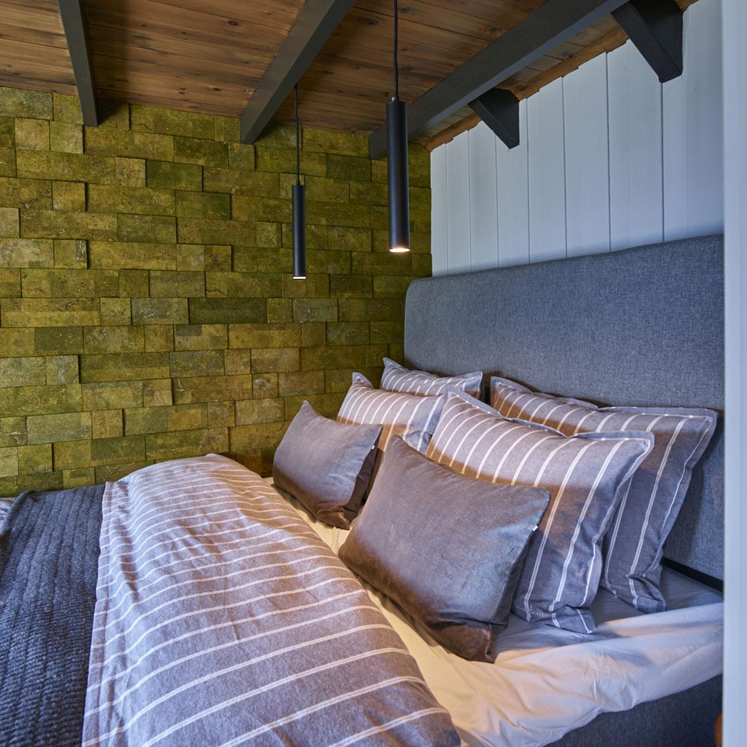 Dobbeltseng på soverom med malt vegg
