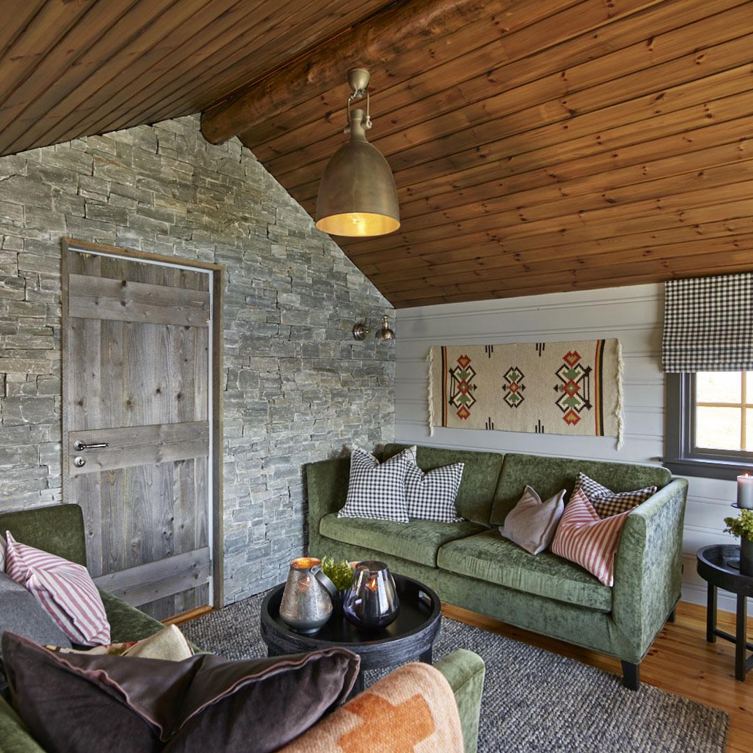 Stue på hytte med grønn sofa og malte vegger og beiset tak