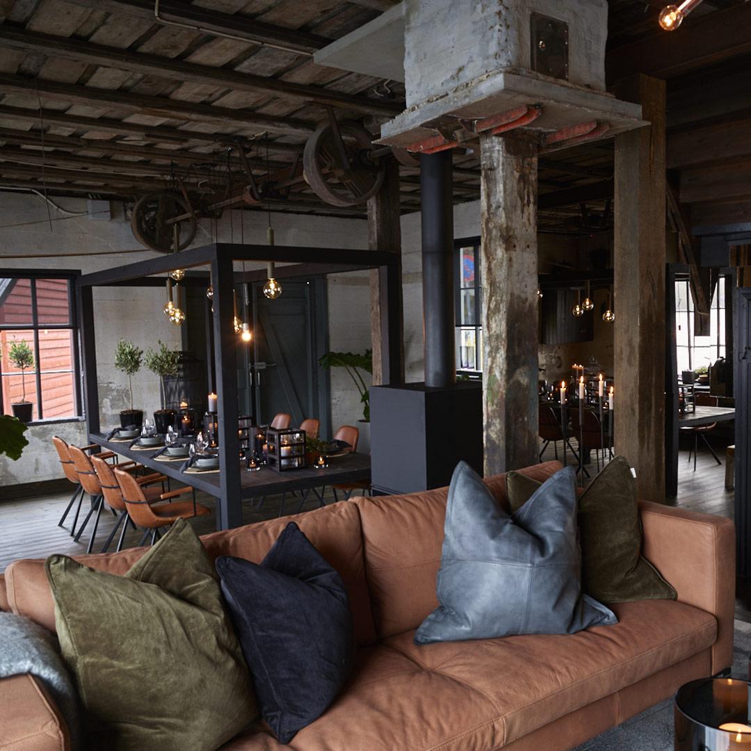 Sofa med puter og langbord i bakgrunnen