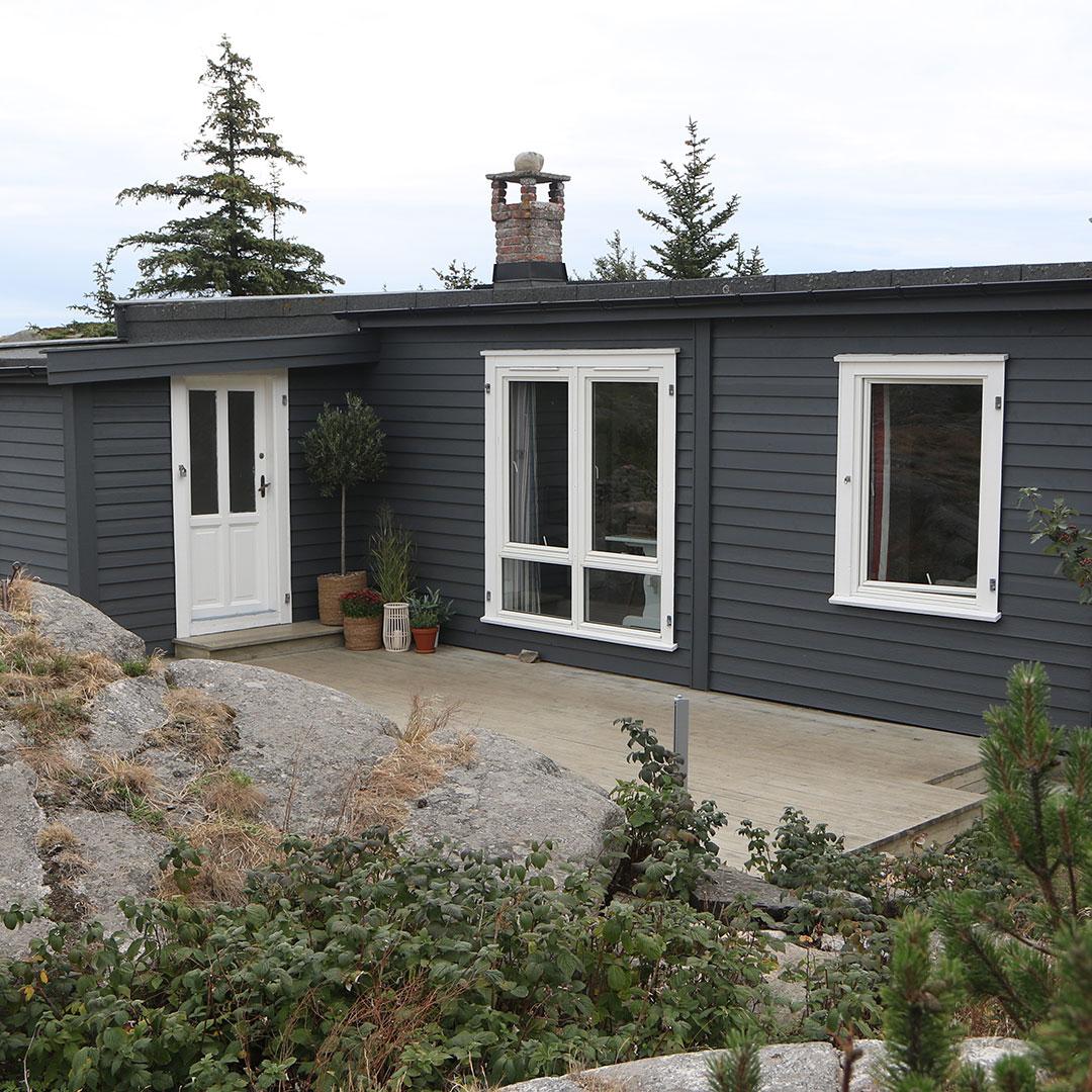 Inngangspartiet til nymalt hytte fra utsiden