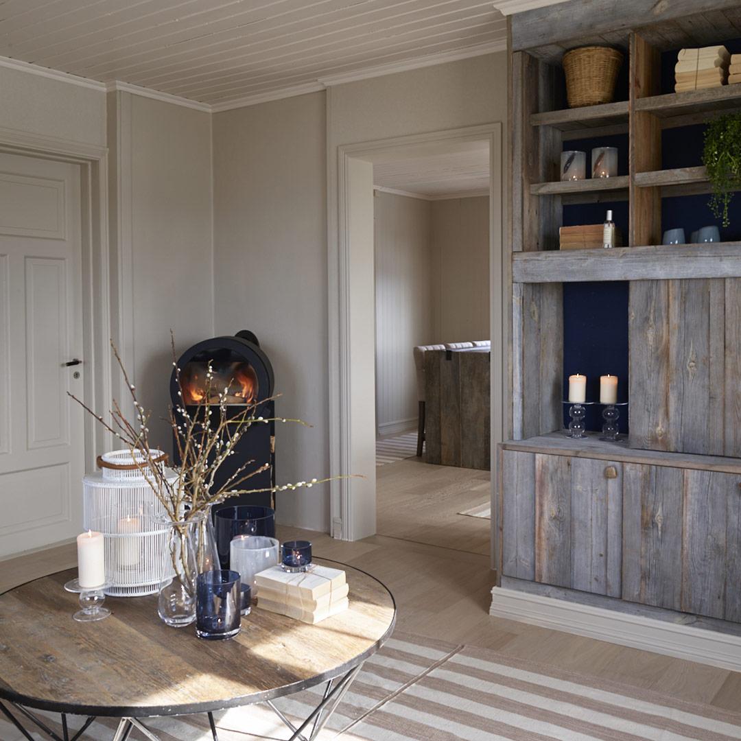 Lys stue med rustikk bokhylle og peis i hjørnet