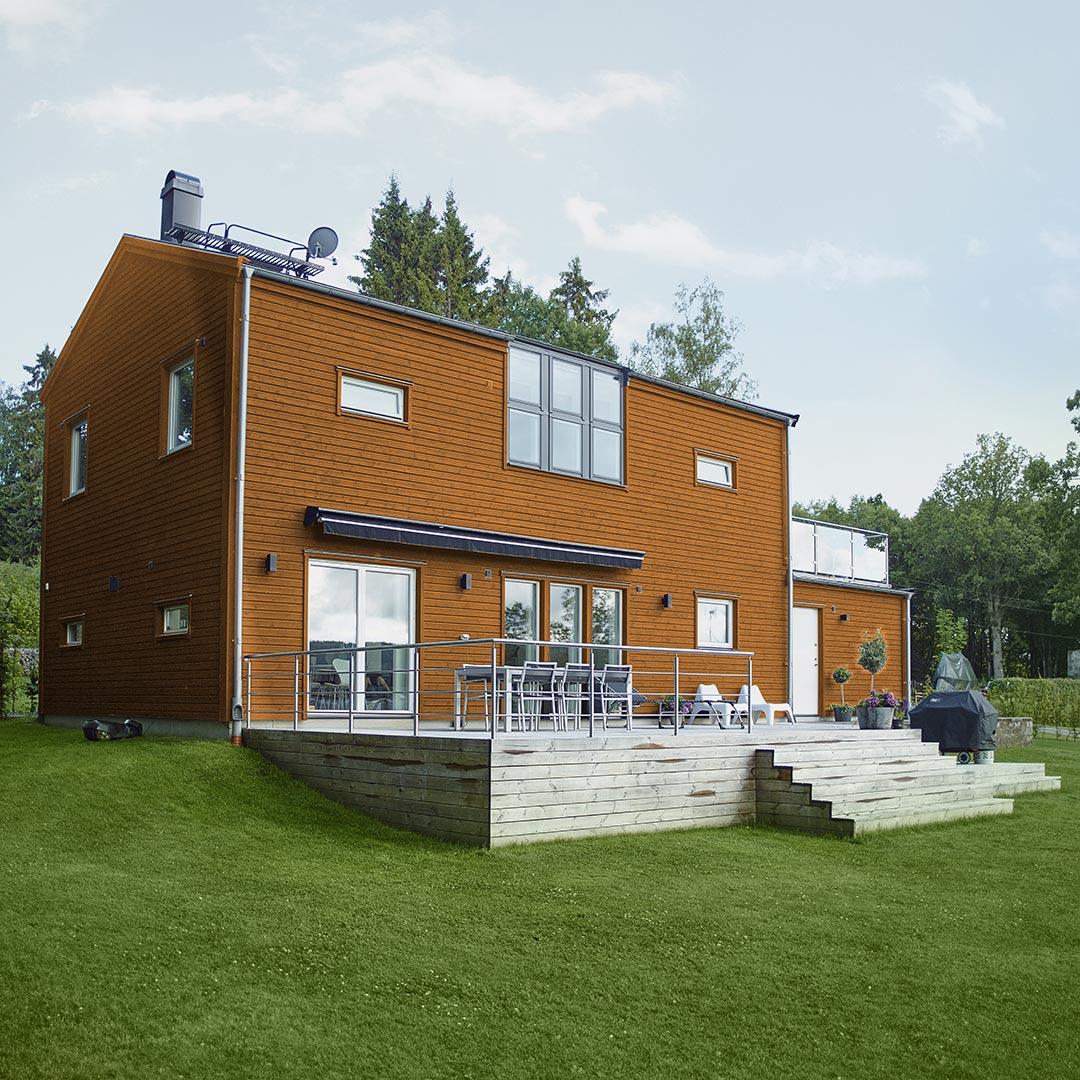 Moderne hus i gulfargen curry med stor hage rundt
