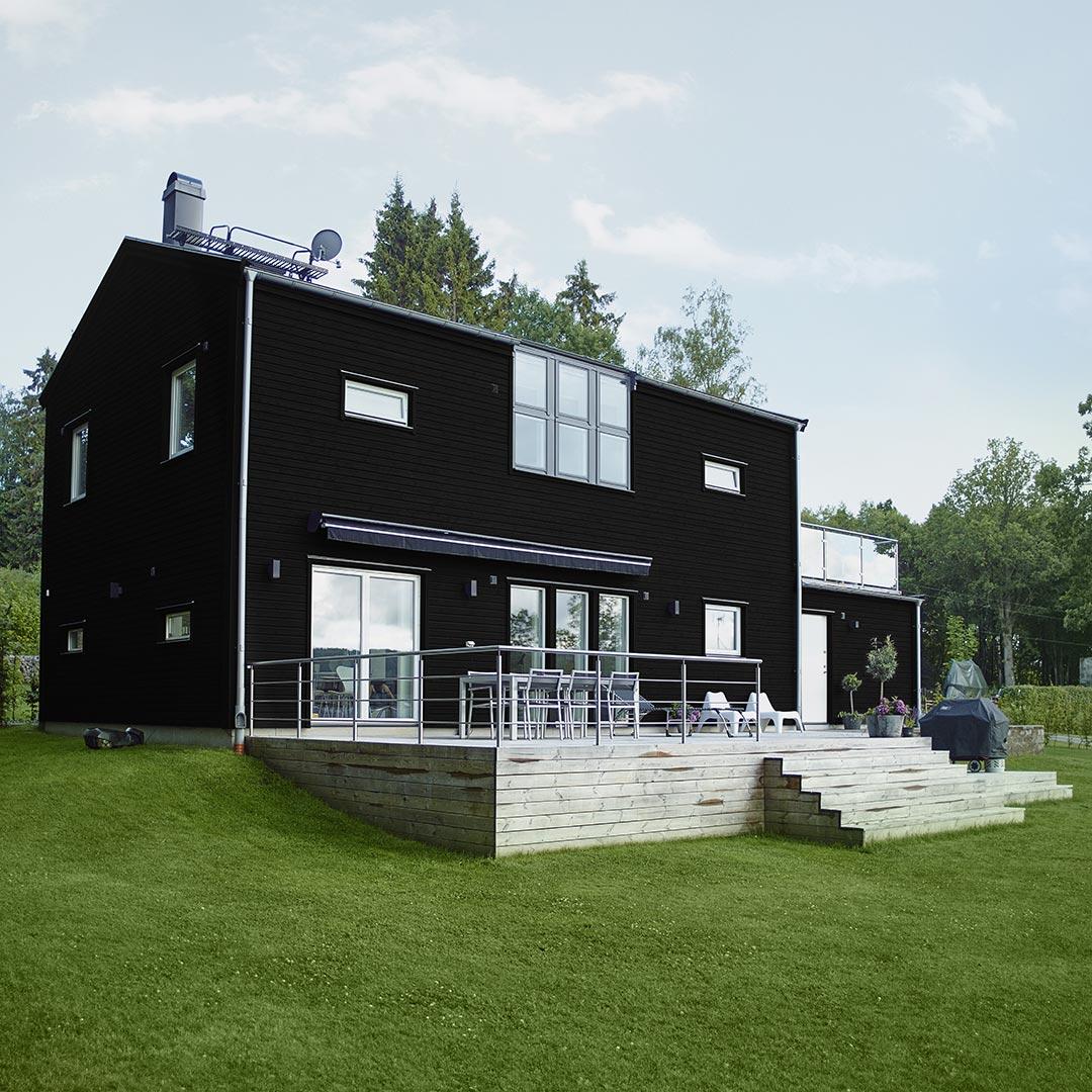 Moderne hus med stor hage malt i mørk farge lakris