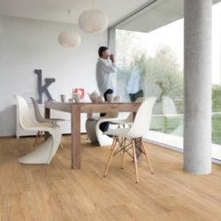 En spiseplass med vindu fra tak til gulv og en mann som nyter utstikten