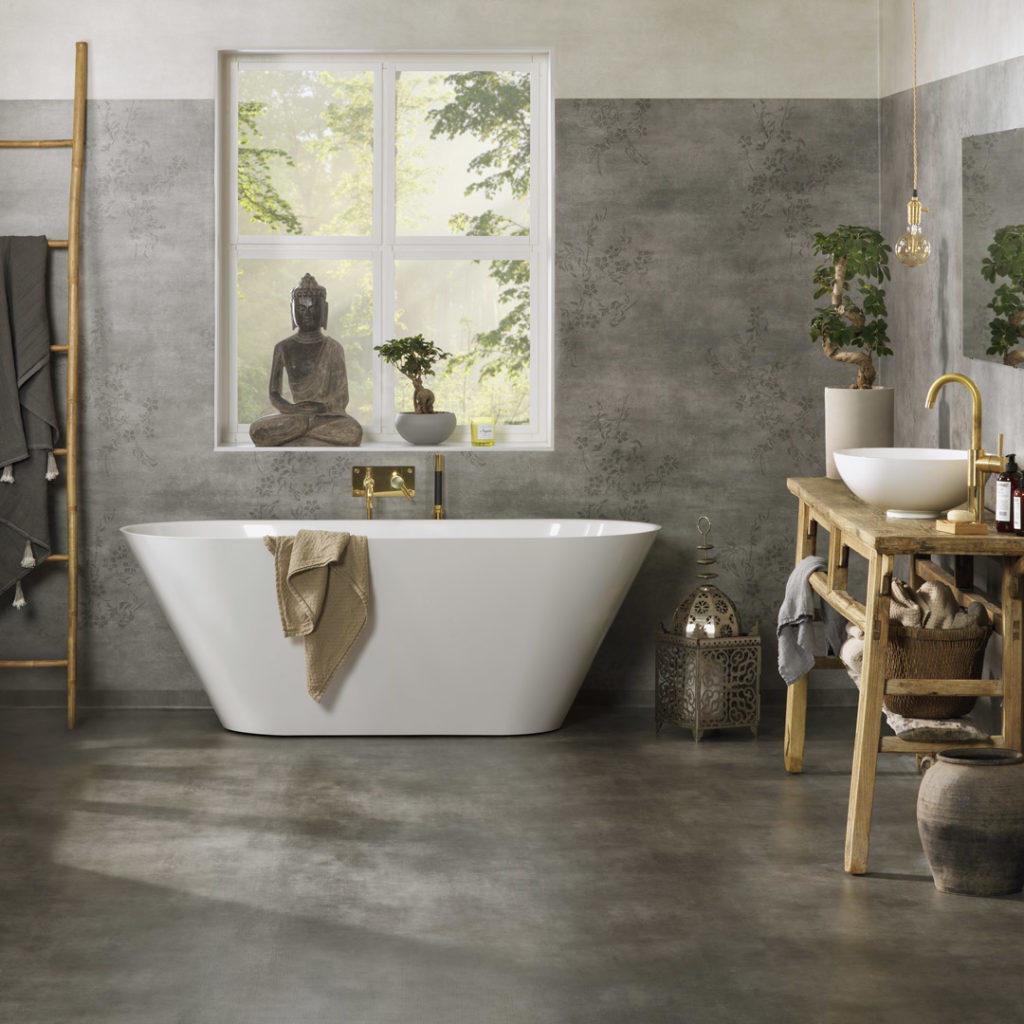Flott bad med grått gulv og et hvit badekar i enden