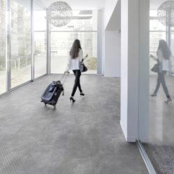 dame med koffert går i en lys gang med grått gulv