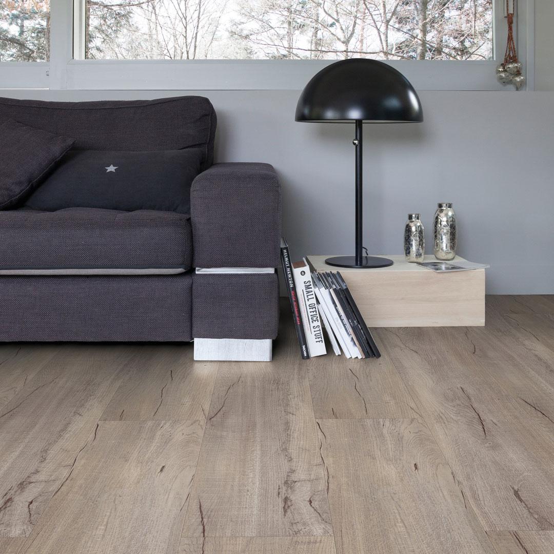 Stue med mørk sofa inntill veggen og mye gulv i forgrunnen