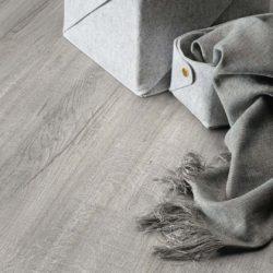 Nærbilde av et stuegulv av typen Klikkvinyl med ullteppe liggende utover