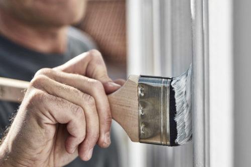 Nærbilde av en som maler husveggen.