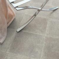 Nærbilde av texline gulv i design colorado beige med utsnitt av et lite bord