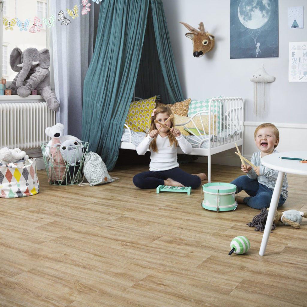 To barn som spiller instrumenter på guvlet på barnerommet
