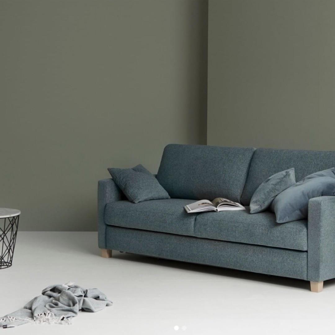 2 seter sofa i blågrå farge foran en vegg med grågrønn farge på veggen