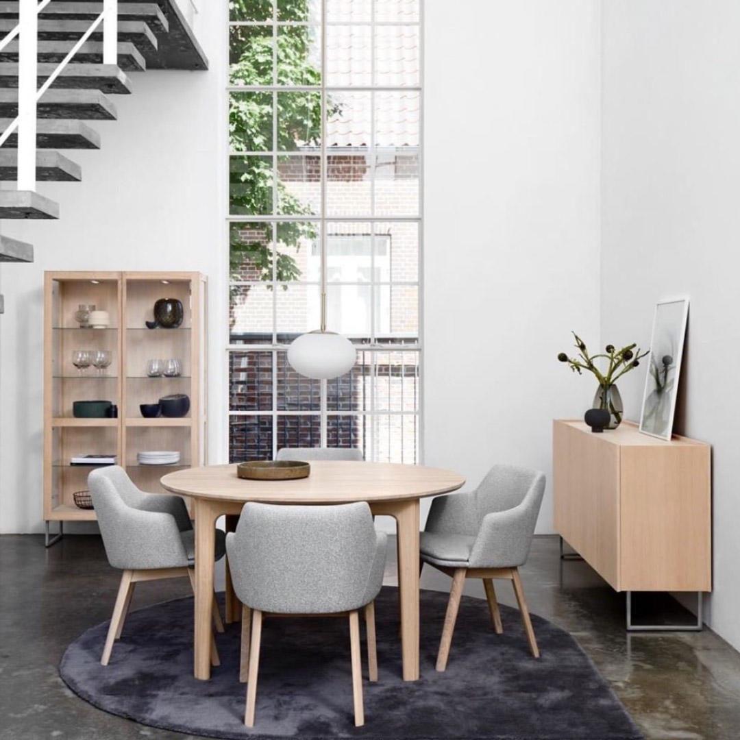 lys spiseplass med rundt bord i et rom med stor høyde under taket, vindu fra gulv til tak i bakgrunnen