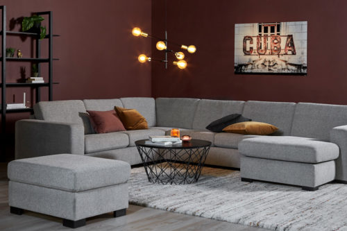 En stor grå sofa i hjørnet av en stue. Veggene er malt med nordisk mørkbrun