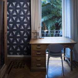 Rustikk skrivepult foran vindu og vegg med blå geometrisk tapet til venstre