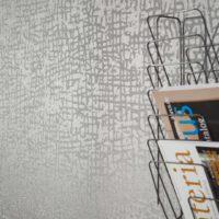 Nærbilde av vegg med tapet i grått mønster med glassperler.