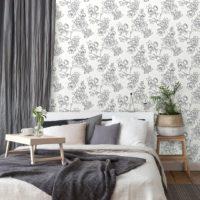 Seng med grå puter og gardin foran en vegg med hvit og grå blomstrete tapet