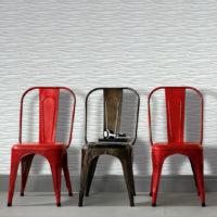 2 rød og 1 brun stol foran vegg med tapet som har lysegrå bølger