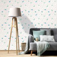 Grå sofa med stålampe i tre foran vegg som ahr hvit tapet med blå grafisk mønster