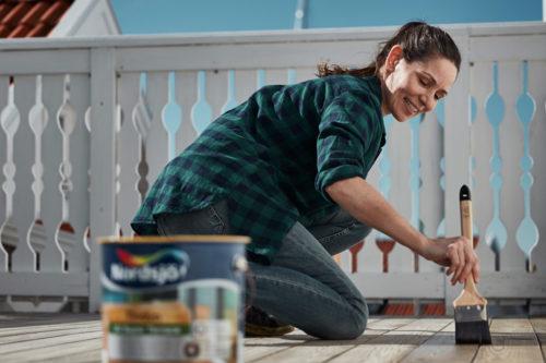en kvinne sitter på kne og beiser terrassen. Bøtte med beis i forgrunnen