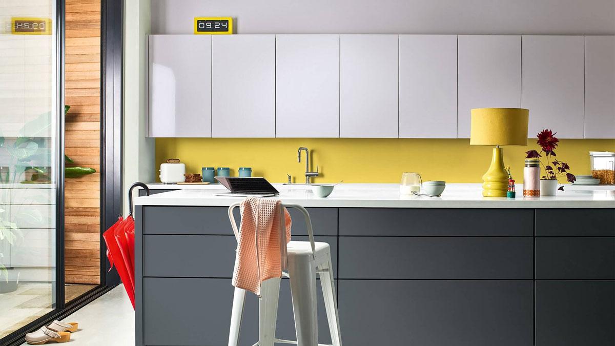 stilrent kjøkken med hvite overskap og mørke grå kjøkkenøy i front
