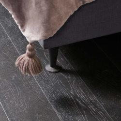 Nærbilde av et mørke grått gulv ved hjørnet av en seng