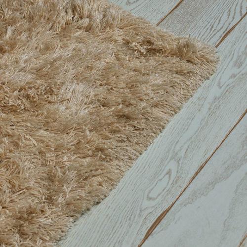 Nærbilde av et parkettgulv med et teppe som dekker litt av gulvet