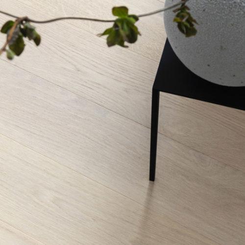 nærbilde av et parkettgulv med lite bord i hjørnet
