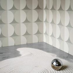 Hjørnet i et rom med beige tapet på veggene og sand + en blank kule på gulvet